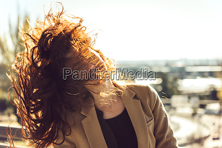 woman tossing red hair during sunny