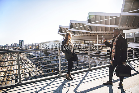 businessman photographing female colleague while standing