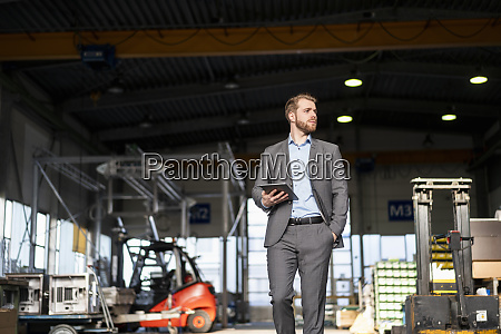 young businessman with tablet walking in