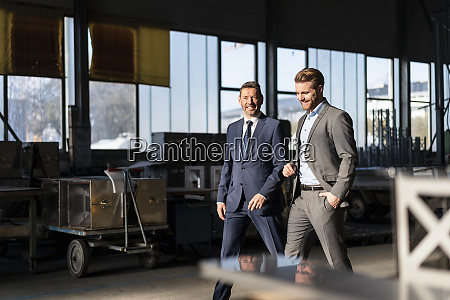 two smiling businessmen walking in a