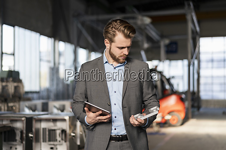 young businessman with tablet and workpiece