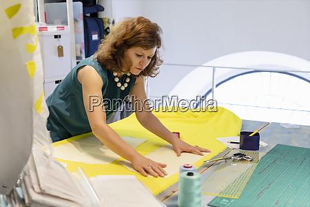 female fashion designer adjusting yellow fabric