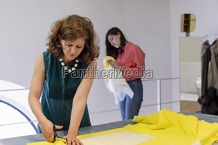 female fashion designer cutting fabric while
