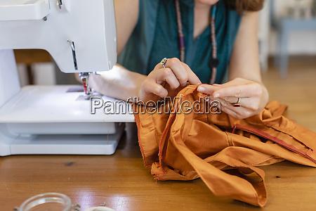 female seamstress sewing orange fabric at