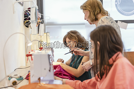 elderly entrepreneur explaining seamstress about designing