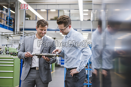 two businessmen examining a product in