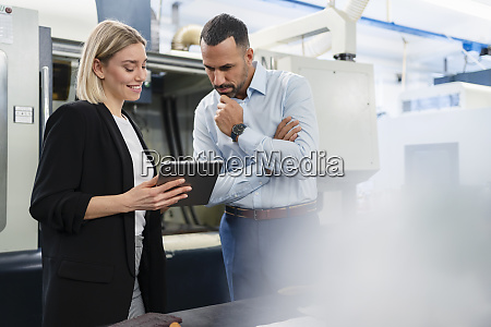 businessman and woman using tablet in
