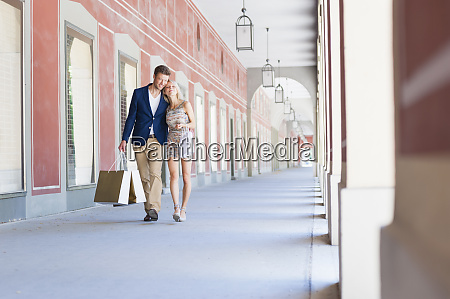 romantic couple with shopping bags walking