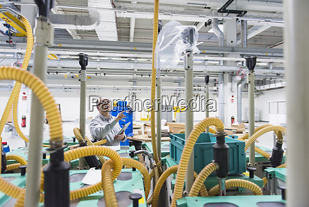 businessman holding tablet in a factory