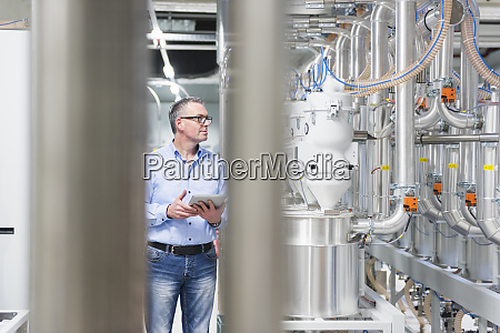 businessman with tablet in a factory