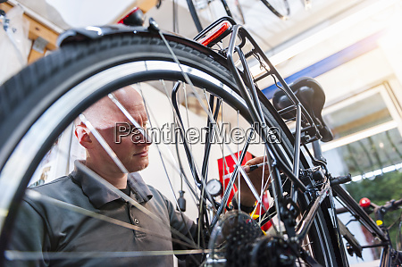 bicycle mechanic working in bike shop