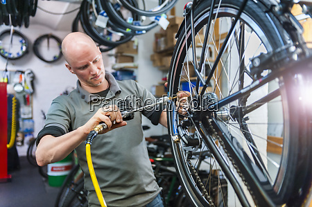 bicycle mechanic working in bike shop