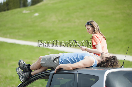 woman reading map while man lying