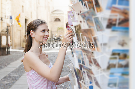 portrait of tourist choosing postcards in