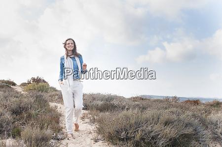 happy woman strolling in beach dunes