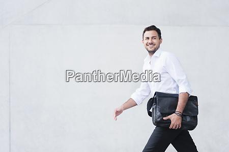 smiling businessman with laptop bag walking