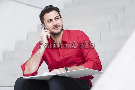 smiling businessman calling with folder sitting