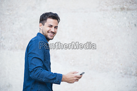 smiling young man with smartphone