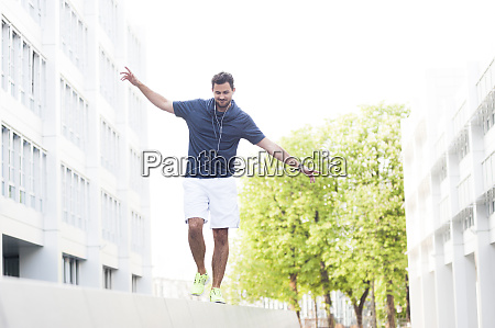 young man balancing on wall in