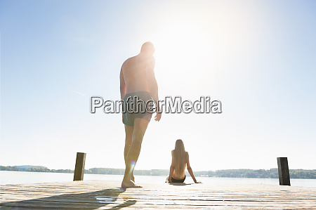 young couple in swimwear on jetty