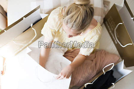 blond woman sitting on bed between