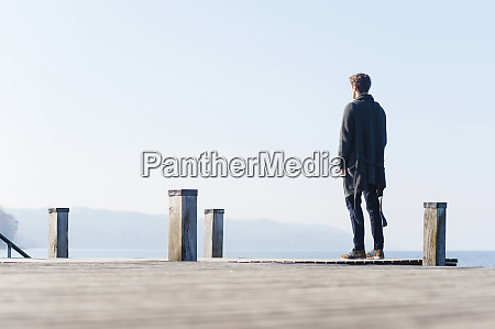man looking at lake against clear
