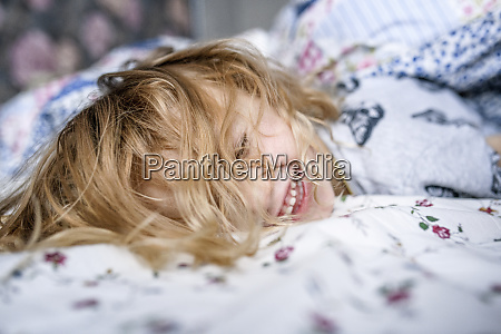 happy girl lying in bed at