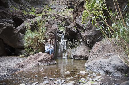 female hiker sitting at waterfall tenerife