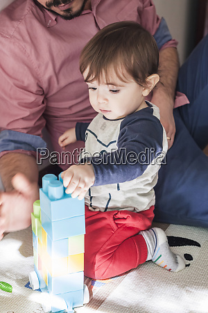 baby boy and father playing with