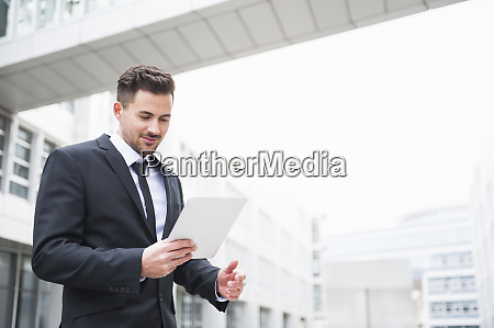 young businessman using digital tablet outside