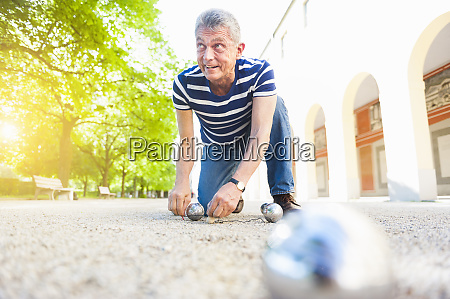 senior boules player kneeling on the
