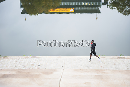 young man jogging at riverside