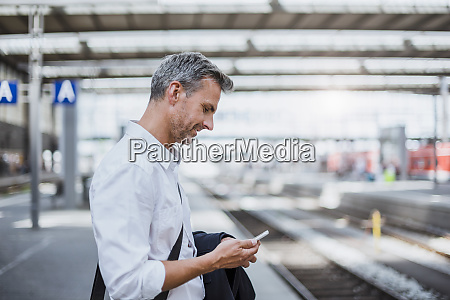 businessman using smart phone while standing