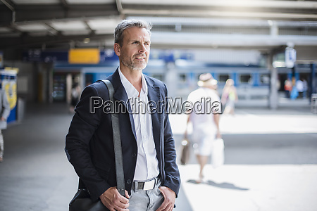 smiling businessman looking away while standing