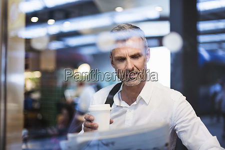 businessman holding coffee reading newspaper while