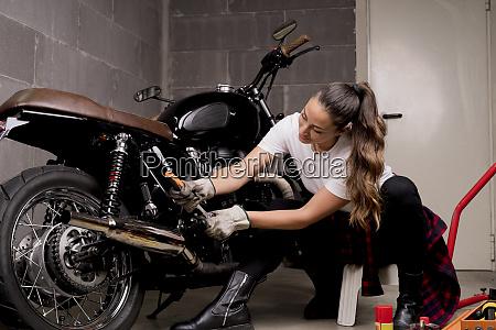 woman repairing motorbike