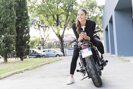 smiling woman sitting on motorbike and