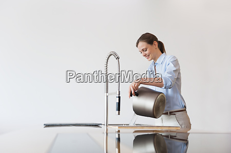 smiling mid adult woman pouring water