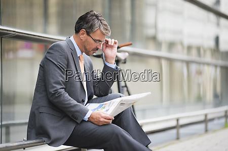 businessman wearing eyeglasses reading newspaper while