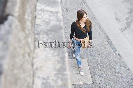 fashionable woman walking on sidewalk in