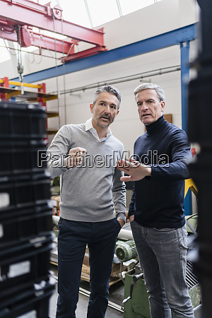 confident male supervisors discussing over production