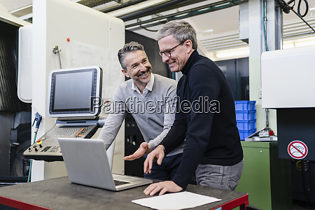 happy male supervisors discussing over laptop