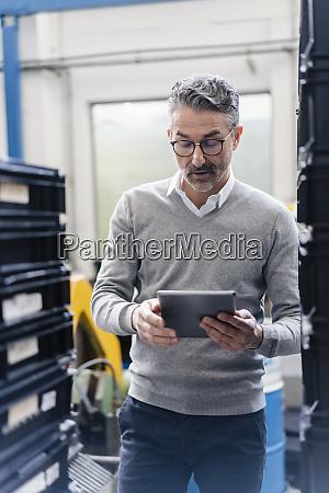 mature male supervisor using digital tablet