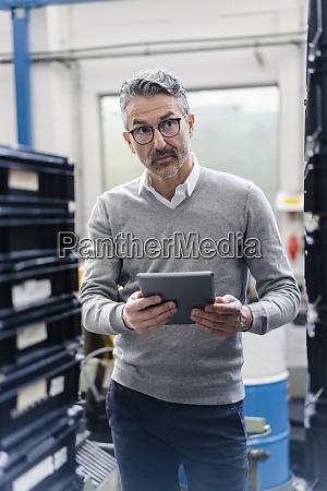 thoughtful male supervisor holding digital tablet