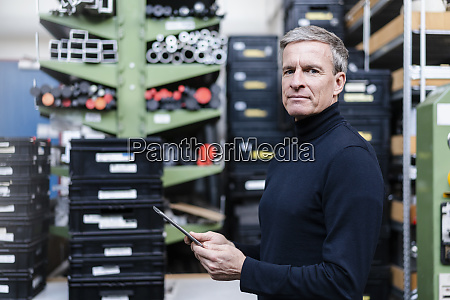 confident male supervisor holding digital tablet