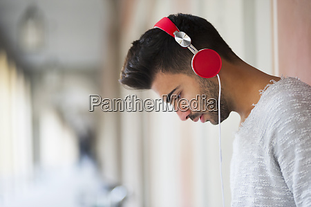 young man listening music through headphones