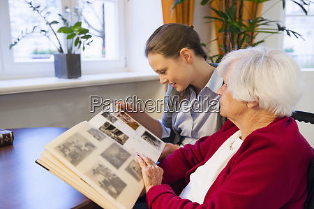 grandmother and granddaughter looking photo album