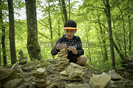 boy stacking stones as cairn in