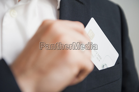 businessman removing credit card from suit