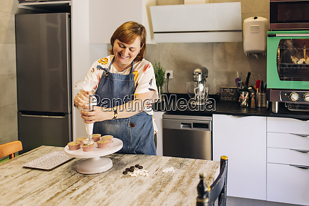 smiling mature woman icing cupcakes on